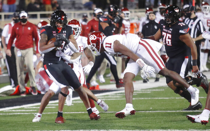 Texas Tech wide receiver Erik Ezukanma is tackled by Oklahoma defensive back TreNorwood during the second half of an NCAA college football game Saturday, Oct. 31, 2020, in Lubbock, Texas. (AP Photo/Mark Rogers)