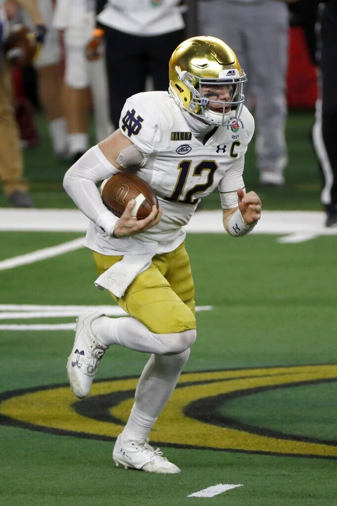 Notre Dame quarterback Ian Book (12) runs the ball in the first half of the Rose Bowl NCAA college football game against Alabama in Arlington, Texas, Friday, Jan. 1, 2021. (AP Photo/Roger Steinman)