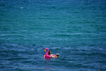 """A couple sunbathe in the sea in Barcelona, Spain, Friday, July 9, 2021. Spain's top diplomat is pushing back against French cautions over vacationing on the Iberian peninsula. Southern Europe's holiday hotspots worry that repeated changes to rules on who can visit is putting people off travel. On Thursday, France's secretary of state for European affairs, Clement Beaune, advised people to """"avoid Spain and Portugal as destinations"""" when booking their holidays because COVID-19 infections are surging there. (AP Photo/Joan Mateu)"""