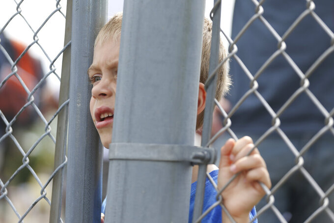 A young fan watches through the fence as pit crews move cars in the garage area before the NASCAR Xfinity Series auto race at Watkins Glen International in Watkins Glen, N.Y., on Saturday, Aug. 7, 2021. (AP Photo/Joshua Bessex)