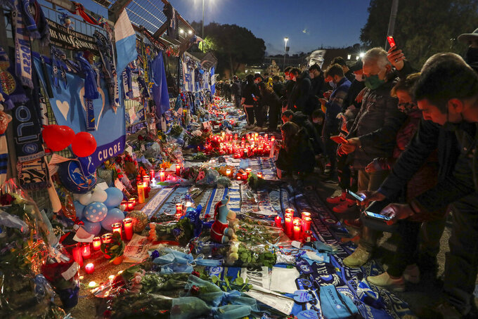 People look memorabilia outside the San Paolo stadium commemorating soccer legend Diego Maradona, in Naples, Thursday, Nov. 26, 2020. Maradona died on Wednesday at the age of 60 of a heart attack in a house outside Buenos Aires where he recovered from a brain operation. (AP Photo/Salvatore Laporta)