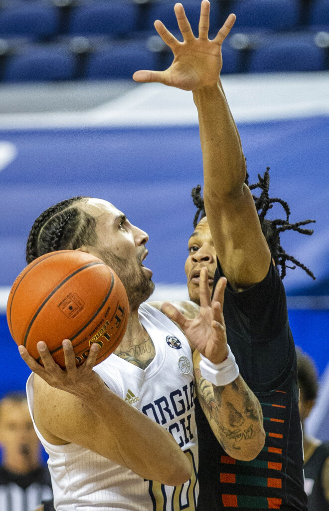 Georgia Tech's Jose Alvarado, left, puts up a shot as Miami's Isaiah Wong defends during an NCAA college basketball game in the quarterfinal round of the Atlantic Coast Conference tournament in Greensboro, N.C., Thursday, March 11, 2021. (Woody Marshall/News & Record via AP)