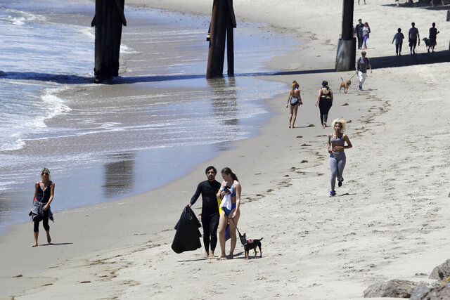 FILE - In this Wednesday, May 13, 2020, file, photo beachgoers walk and exercise on the beach in Malibu, Calif. Masks are required at Los Angeles County beaches, which reopened Wednesday to join counterparts in other states that have allowed a somewhat limited return to famed stretches of sand. (AP Photo/Marcio Jose Sanchez, File)