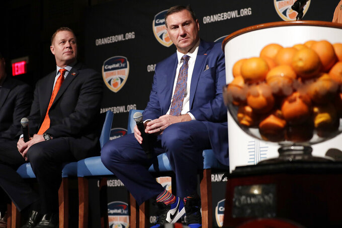 Virginia head coach Bronco Mendenhall, left, and Florida head coach Dan Mullen, right, listen during a news conference for the Orange Bowl NCAA college football game, Wednesday, Dec. 11, 2019, in Hollywood, Fla. Florida plays Virginia in the Orange Bowl Dec. 30 at Hard Rock Stadium in Miami Gardens, Fla. (AP Photo/Lynne Sladky)