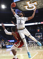 Georgia Tech forward James Banks III gets the offensive rebound over Elon forward Federico Poser during the second half of an NCAA college basketball game on Monday, Nov. 11, 2019, in Atlanta. Georgia Tech won, 64-41. (Curtis Compton/Atlanta Journal-Constitution via AP)