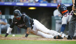 Colorado Rockies' Ian Desmond, left, scores on a single hit by Tony Wolters as Houston Astros catcher Robinson Chirinos loses the ball in the fifth inning of a baseball game Tuesday, July 2, 2019, in Denver. (AP Photo/David Zalubowski)