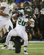 South Florida running back Johnny Ford (20) is tackled by Tulsa safety Manny Bunch, bottom, and safety McKinley Whitfield, top, in the first half of an NCAA college football game in Tulsa, Okla., Friday, Oct. 12, 2018. (AP Photo/Sue Ogrocki)