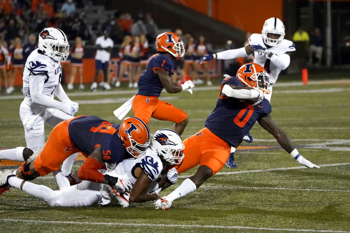 Illinois running back Joshua McCray (0) is tackled by UTSA's Jamal Ligon while carrying the ball during the first half of an NCAA college football game Saturday, Sept. 4, 2021, in Champaign, Ill. (AP Photo/Charles Rex Arbogast)