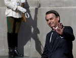 Brazil's President Jair Bolsonaro waves to reporters as he arrives to La Moneda presidential palace in Santiago, Chile, Friday, March 22, 2019. South American heads of state are meeting in Santiago to discuss the development of a new regional political bloc called Prosur, the idea being to replace the Unasur, the current body that many describe as defunct. (AP Photo/Esteban Felix)