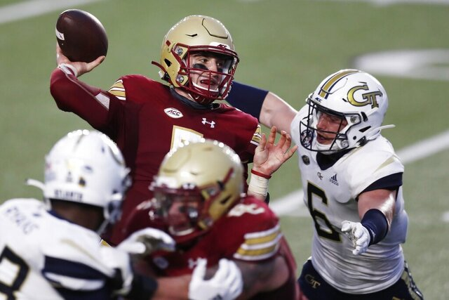 Boston College quarterback Phil Jurkovec, top left, passes under pressure from Georgia Tech linebacker David Curry (6) during the first half of an NCAA college football game, Saturday, Oct. 24, 2020, in Boston. (AP Photo/Michael Dwyer)