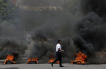 A man crosses a street blocked by a burning barricade during a protest to demand the resignation of President Juan Orlando Hernandez, in Tegucigalpa, Honduras, Thursday, Oct. 24 2019. Calls for President Hernandez's resignation came after his younger brother was convicted on drug trafficking charges in New York and testimony implicated the president in his drug enterprise. (AP Photo/Elmer Martinez)