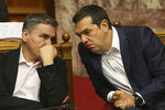 Greek Prime Minister Alexis Tsipras, right, and Finance Minister Euclid Tsakalotos talk during a parliamentary session in Athens, on Thursday, June 14, 2018. The head of Greece's main opposition party Kyriakos Mitsotakis submitted a motion for a no-confidence vote in the government, objecting to a deal reached between the prime ministers of Greece and Macedonia to settle a decades-old dispute over Macedonia's name. (AP Photo/Petros Giannakouris)