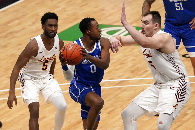Drake's D.J. Wilkins (0) passes as Loyola of Chicago's Keith Clemons (5) and Cameron Krutwig defend during the first half of the championship game in the NCAA Missouri Valley Conference men's basketball tournament Sunday, March 7, 2021, in St. Louis. (AP Photo/Jeff Roberson)