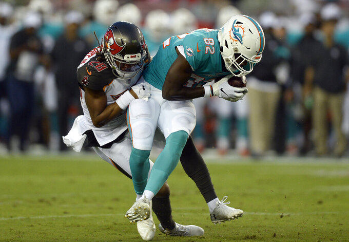 Tampa Bay Buccaneers cornerback Vernon Hargreaves III (28) wraps up Miami Dolphins wide receiver Preston Williams (82) after a reception during the first half of an NFL preseason football game Friday, Aug. 16, 2019, in Tampa, Fla. (AP Photo/Jason Behnken)