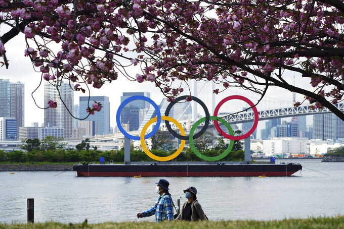 Under blooming cherry blossoms, people wearing protective masks to help curb the spread of the coronavirus walk with a backdrop of the Olympic rings floating in the water in the Odaiba section Thursday, April 8, 2021, in Tokyo. Many preparations are still up in the air as organizers try to figure out how to hold the postponed games in the middle of a pandemic. (AP Photo/Eugene Hoshiko)