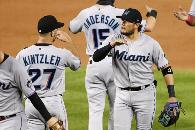 Miami Marlins' Miguel Rojas, right, and Brandon Kintzler (27) celebrate after a baseball game against the Washington Nationals, Friday, Aug. 21, 2020, in Washington. The Marlins won 3-2. (AP Photo/Nick Wass)