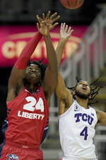 Liberty's Micaiah Abii (24) and TCU's PJ Fuller (4) battle for a rebound during the first half of an NCAA college basketball game Sunday, Nov. 29, 2020, at the T-Mobile Center in Kansas City, Mo. (AP Photo/Charlie Riedel)