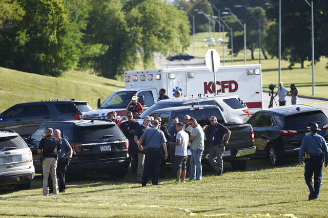 Law enforcement agents confer near the site of a shooting Thursday, July 2, 2020, in Kansas City, Mo. The shooting left a suspect dead and a police officer in critical condition after being shot in the head. The officer was hospitalized for emergency surgery, Kansas City police said on Twitter. (Tammy Ljungblad/The Kansas City Star via AP)
