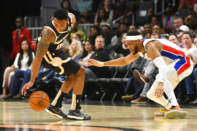 Atlanta Hawks guard Jeff Teague reaches for the ball lost by Detroit Pistons guard Bruce Brown, right, during the first half of an NBA basketball game Saturday, Jan. 18, 2020, in Atlanta. (AP Photo/John Amis)