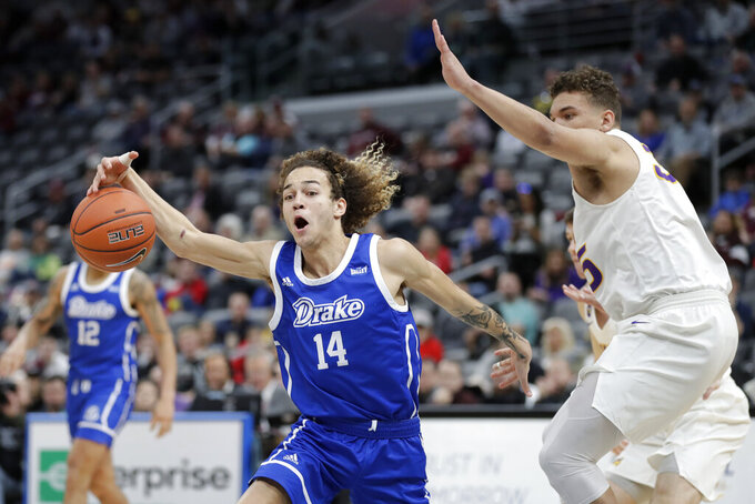 Drake's Noah Thomas (14) reaches for the ball as Northern Iowa's Noah Carter, right, watches during the first half of an NCAA college basketball game in the quarterfinal round of the Missouri Valley Conference men's tournament Friday, March 6, 2020, in St. Louis. (AP Photo/Jeff Roberson)