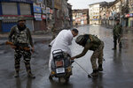 Indian Paramilitary soldiers check the bag of a man riding a scooter during curfew in Srinagar, Indian controlled Kashmir, Thursday, Aug. 8, 2019. The lives of millions in India's only Muslim-majority region have been upended since the latest, and most serious, crackdown followed a decision by New Delhi to revoke the special status of Jammu and Kashmir and downgrade the Himalayan region from statehood to a territory. Kashmir is claimed in full by both India and Pakistan, and rebels have been fighting Indian rule in the portion it administers for decades. (AP Photo/Dar Yasin)