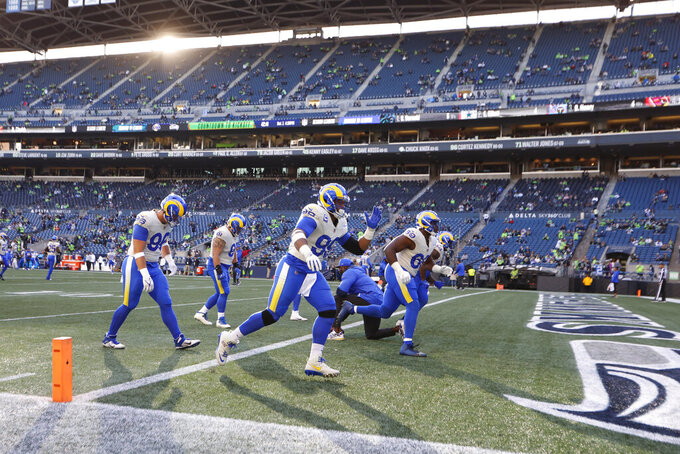 CORRECTS TO LUMEN FIELD NOT CENTURYLINK FIELD - Los Angeles Rams players, including defensive end Aaron Donald, center, warm up at Lumen Field before an NFL football game against the Seattle Seahawks, Thursday, Oct. 7, 2021, in Seattle. (AP Photo/Craig Mitchelldyer)