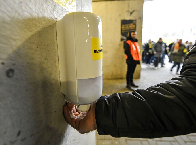 "FILE - In this Feb. 29, 2020, file photo, a fan washes his hands at a new disinfection station in the stadium prior the German Bundesliga soccer match between Borussia Dortmund and SC Freiburg in Dortmund, Germany. ""In large masses, there is no system that can effectively prevent another person from giving germs to a second individual,"" said Philip Tierno, a clinical professor of pathology at New York University's Grossman School of Medicine. (AP Photo/Martin Meissner, File)"