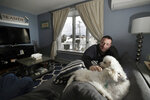 In this Jan. 23, 2019 photo, Denis Champagne, Jr. plays with his dogs Maebelle and Isabel at home near the coast in Salisbury, Mass. Academic researchers say concerns over rising sea levels and increased flooding are having subtle but significant impacts on coastal property values, finding that climate change concerns have sapped more than $15 billion in appreciation from homes along the Eastern Seaboard and Gulf Coast. (AP Photo/Elise Amendola)