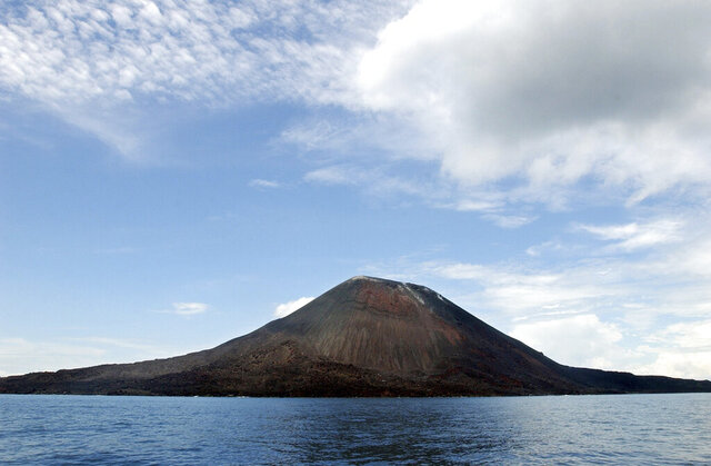 FILE - This April 10, 2004 file photo shows the volcano, Anak Krakatau, seen from the coast of West Java, Indonesia. Indonesia's Anak Krakatau in Lampung erupted on Friday night, April 10, 2020,  Indonesia's volcanology agency said the eruption is spewing the column of ash up to 500 meter high.(AP Photo/Suzanne Plunkett, File)