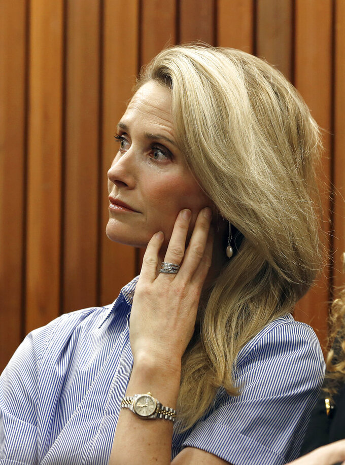 """FILE - In this May 9, 2019 file photo First partner Jennifer Siebel Newsom listens as her husband, Gov. Gavin Newsom, discusses his revised state budget during a news conference, in Sacramento, Calif. California Gov. Gavin Newsom said he """"absolutely"""" sees no conflict of interest with a nonprofit launched by his wife accepting donations from companies that lobby his administration.  (AP Photo/Rich Pedroncelli,File)"""