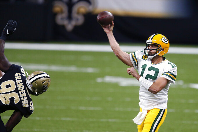 Green Bay Packers quarterback Aaron Rodgers (12) passes under pressure from New Orleans Saints defensive end Carl Granderson (96) in the first half of an NFL football game in New Orleans, Sunday, Sept. 27, 2020. (AP Photo/Butch Dill)