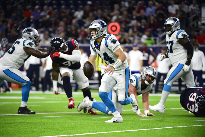 Carolina Panthers quarterback Sam Darnold (14) scramble out of the pocket during the first half of an NFL football game against the Houston Texans Thursday, Sept. 23, 2021, in Houston. (AP Photo/Justin Rex)