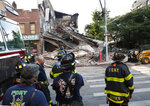 Firefighters stand near a collapsed multistory building Wednesday, July 1, 2020, in the Carroll Gardens neighborhood of the Brooklyn borough of New York. The building, which housed a health club, had been shuttered during the coronavirus pandemic. Just three weeks earlier, building inspectors had ordered a halt to some construction work at the location because of structural problems. (AP Photo/Kathy Willens)
