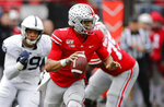 Ohio State quarterback Justin Fields, right, looks for an open receiver as Penn State defensive lineman Yetur Gross-Matos chases him during the second half of an NCAA college football game Saturday, Nov. 23, 2019, in Columbus, Ohio. Ohio State beat Penn State 28-17. (AP Photo/Jay LaPrete)