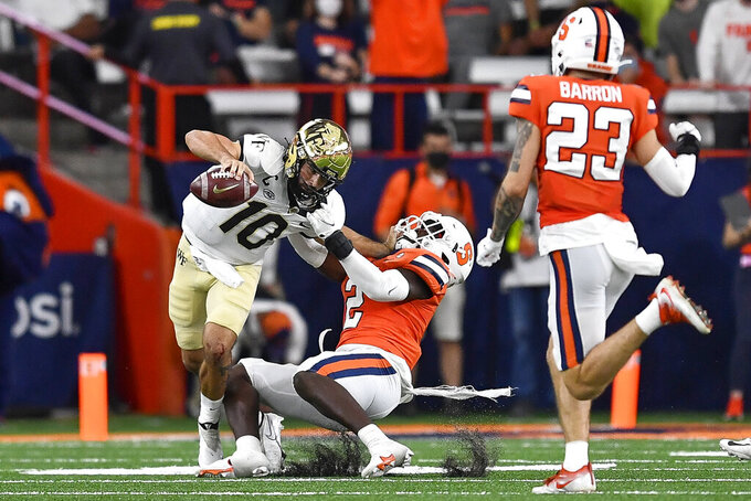 Wake Forest quarterback Sam Hartman (10) is tackled by Syracuse linebacker Marlowe Wax (2) during the first half of an NCAA college football game in Syracuse, N.Y., Saturday, Oct. 9, 2021. (AP Photo/Adrian Kraus)