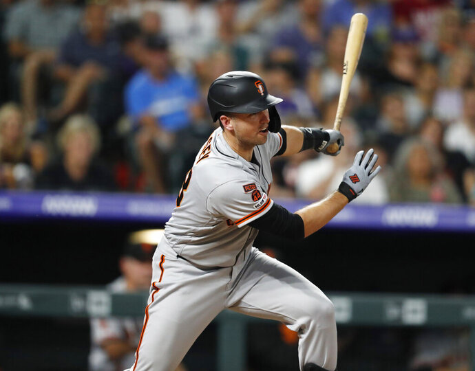 San Francisco Giants pinch-hitter Buster Posey watches his tow-run double off Colorado Rockies relief pitcher Carlos Estevez during the eighth inning of a baseball game Saturday, Aug. 3, 2019, in Denver. (AP Photo/David Zalubowski)