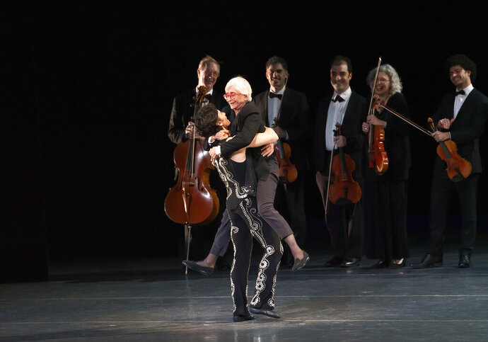 In this Saturday, Oct. 26, 2019, photo provided by the American Ballet Theatre, Herman Cornejo lifts Twyla Tharp during the curtain call of the celebration of Herman Cornejo's 20th Anniversary with American Ballet Theatre in New York. Cornejo has been a favorite of New York ballet audiences ever since he set foot on the American Ballet Theatre stage 20 years ago. (Kyle Froman via AP)