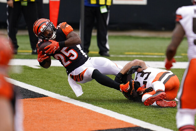 Cincinnati Bengals' Giovani Bernard (25) goes in for a touchdown while being tackled by Cleveland Browns' Andrew Sendejo (23) during the second half of an NFL football game, Sunday, Oct. 25, 2020, in Cincinnati. (AP Photo/Michael Conroy)