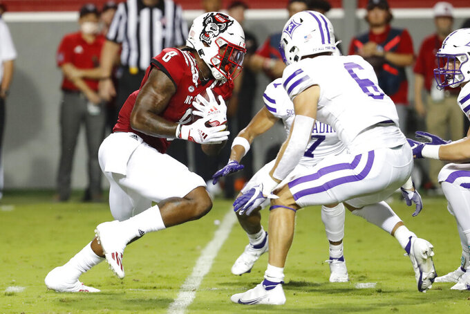 North Carolina State's Ricky Person Jr. (8) runs the ball between Furman's DiMarcus Clay (7) and Hugh Ryan (6) during the first half of an NCAA college football game in Raleigh, N.C., Saturday, Sept. 18, 2021. (AP Photo/Karl B DeBlaker)