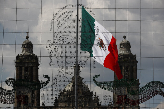 An image of Leona Vicario, to be illuminated after dark, hangs in front of the Metropolitan Cathedral ahead of the annual shout of independence, in the Zocalo, Mexico City, Tuesday, Sept. 15, 2020. Instead of the throngs of supporters who pack the Zocalo in a typical year, this Independence Day, with the coronavirus pandemic ongoing, President Andres Manuel Lopez Obrador will look out over an empty plaza as he gives the traditional