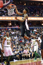 Washington Wizards forward Devin Robinson dunks against Boston Celtics guard PJ Dozier (50) during the second half of an NBA basketball game Tuesday, April 9, 2019, in Washington. The Celtics won 116-110. (AP Photo/Nick Wass)