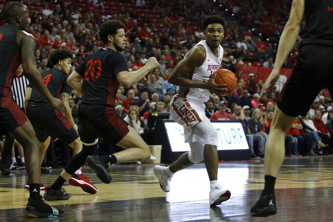 UNLV's Bryce Hamilton (13) drive against San Diego State's Jordan Schakel (20) during the first half of an NCAA college basketball game on Sunday, Dec. 26, 2020, in Las Vegas. (AP Photo/Joe Buglewicz)
