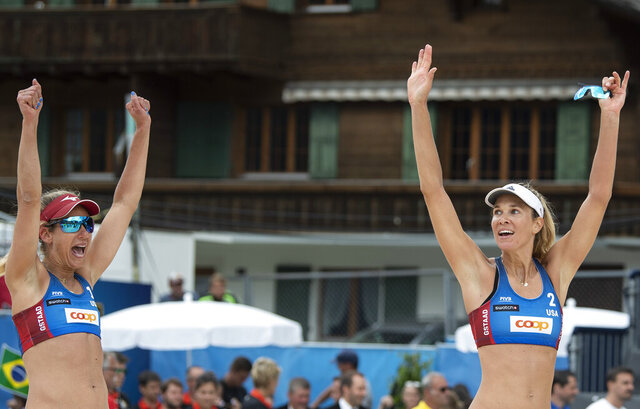 FILE - In this July 14, 2019, file photo, April Ross, left, and Alix Klineman, of the United States, celebrate their victory after the women's gold medal game at the Beachvolley Worldtour Major Series in Gstaad, Switzerland. With her usual practice sites closed down, two-time Olympic medalist April Ross managed to build her own beach volleyball court with supplies she picked up at Home Depot. What's proven to be a more difficult adjustment to the coronavirus pandemic: Remembering not to high-five her partner Alix Klineman during their workouts. (Peter Schneider/Keystone via AP, FIile)