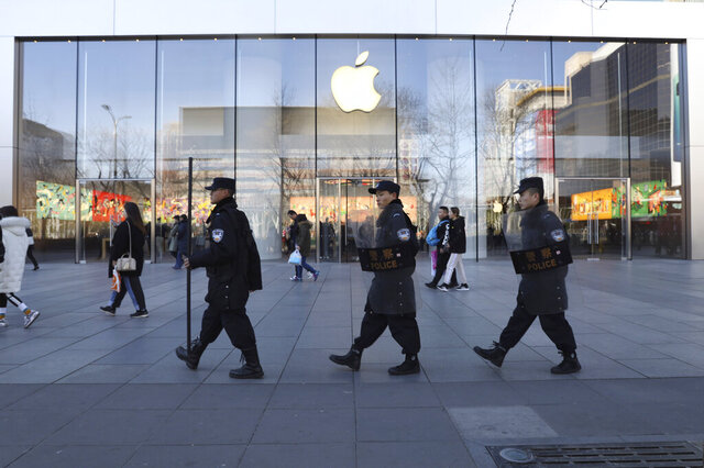 FILE - In this March 6, 2019, file photo, Chinese security guards march past an Apple store in Beijing, China. Apple is temporarily closing its 42 stores in mainland China, one of its largest markets, as a new virus spreads rapidly and the death toll there rose to 259 on Saturday, Feb. 1, 2020. The iPhone maker said in a statement it was closing stores, corporate offices and contact centers in China until Feb. 9