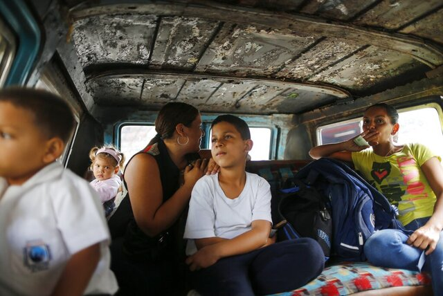 Passengers ride on public transport in Caracas, Venezuela, Wednesday, Feb. 19, 2020. The debate over fresh U.S. sanctions aimed at forcing out Venezuela's Nicolás Maduro played out Wednesday across the crisis-stricken South American nation. Families have been split up with at least 4.5 million Venezuelans fleeing crumbling public services. (AP Photo/Ariana Cubillos)