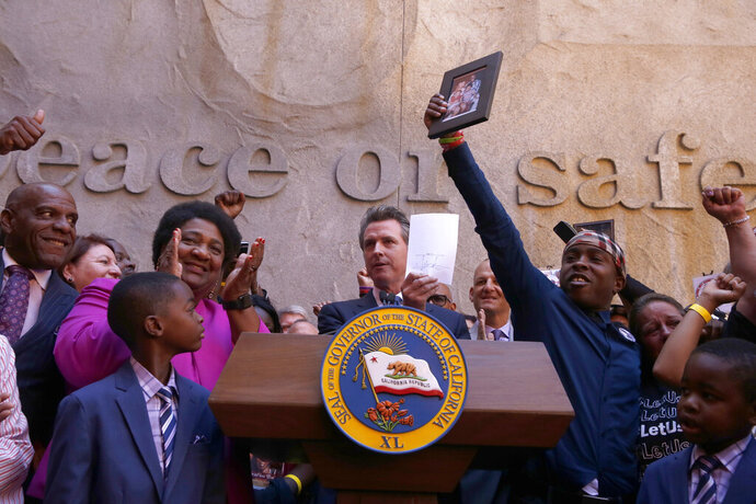 FILE - In this Aug. 9, 2019 file photo Gov. Gavin Newsom holds up the measure by Assemblywoman Shirley Weber, D-San Diego, left, that he signed that limits the use of lethal force by law enforcement, in Sacramento, Calif. The new law will allow police to use deadly force only when