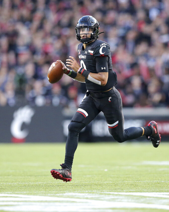 Cincinnati quarterback Desmond Ridder rolls out of the pocket during the first half of the team's NCAA college football game against UCLA on Thursday, Aug. 29, 2019, in Cincinnati. (Kareem Elgazzar/The Cincinnati Enquirer via AP)