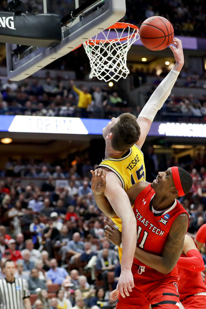 Michigan center Jon Teske shoots over Texas Tech forward Tariq Owens during the first half an NCAA men's college basketball tournament West Region semifinal Thursday, March 28, 2019, in Anaheim, Calif. (AP Photo/Marcio Jose Sanchez)