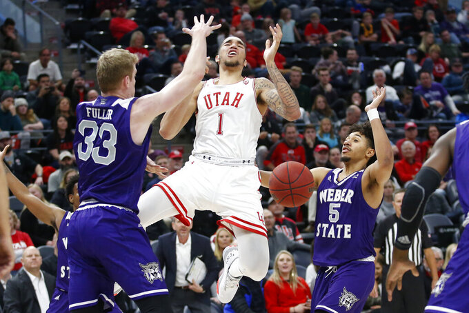 Weber State's Tim Fuller (33) and Cody John (5) defend against Utah forward Timmy Allen (1) in the second half during an NCAA college basketball game Saturday, Dec. 14, 2019, in Salt Lake City. (AP Photo/Rick Bowmer)
