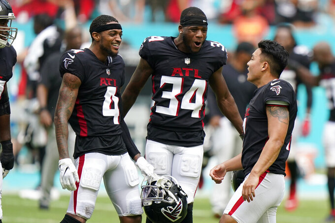 Atlanta Falcons wide receiver Tajae Sharpe (4) and cornerback Darren Hall (34) congratulate kicker Younghoe Koo (7) after he kicked the game-winning field goal during the second half of an NFL football game against the Miami Dolphins, Sunday, Oct. 24, 2021, in Miami Gardens, Fla. The Falcons defeated the Dolphins 30-28. (AP Photo/Wilfredo Lee)
